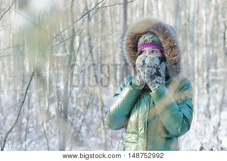 Young woman in winter frost forest is hiding her face in woolly scarf and mittens outdoors