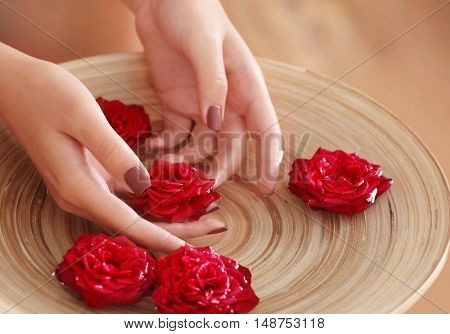Female hands in spa wooden bowl with flowers, closeup