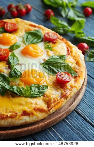 Margarita pizza with basil leaves and egg on wooden table closeup