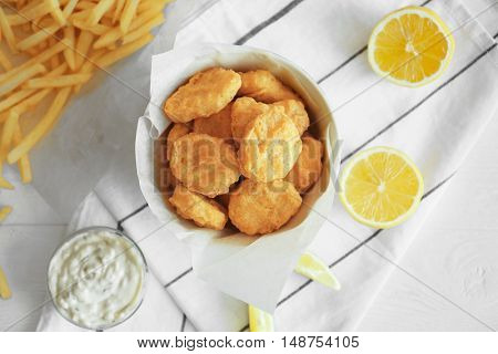 Tasty nuggets in plate and lemon on napkin