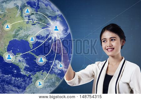 Concept of social media connection. Beautiful businesswoman pressing button on the virtual screen with social media icon and globe