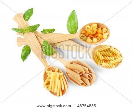 Wooden spoons with pasta and basil leaves, isolated on white