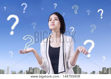 Picture of a confused female worker thinking idea with question marks on the sky