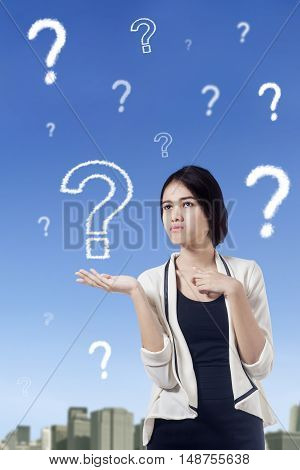Portrait of a young businesswoman looks confused with question marks on the sky