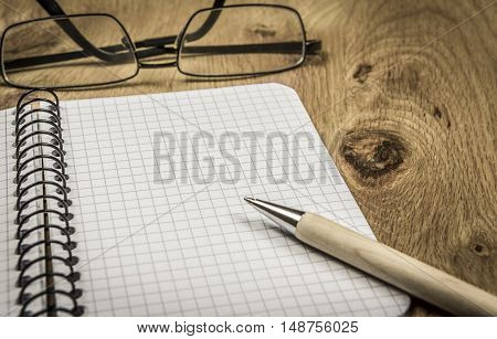 Maths notebook and eyeglasses on wooden desk - Graphic spiral notebook with copy space and eyeglasses on wooden desk in vintage settings