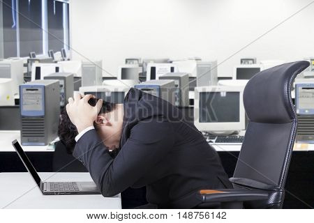 Portrait of stressful male entrepreneur sitting on chair while working with laptop computer in the office