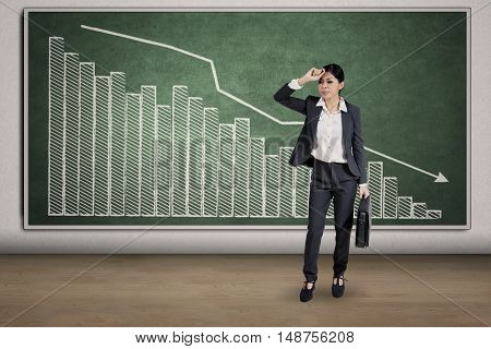 Full length of young businesswoman looks depressed and standing in front of declining financial graph