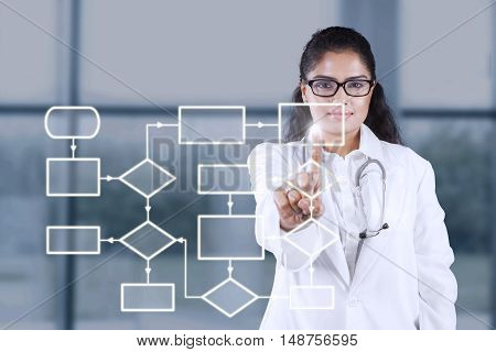 Picture of female doctor pressing a button of workflow scheme on the futuristic screen in hospital