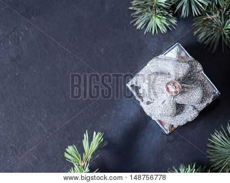 Blue spruce branches with decorative gift ornament on dark black concrete effect background. Copy space