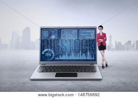 Young businessperson leans on laptop with financial chart on the screen shot outdoors