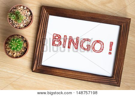 Bingo, text message on wood frame board on wood table / business concept / Top view