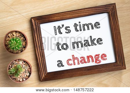 it's time to make a change, text message on wood frame board on wood table / business concept / Top view