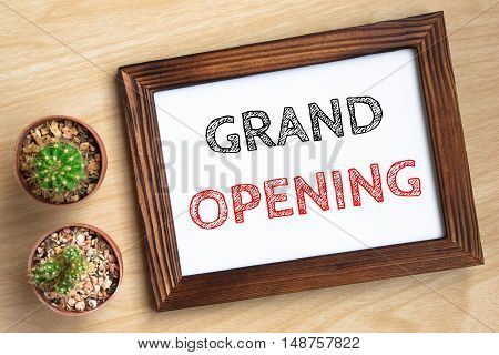 grand opening, text message on wood frame board on wood table / business concept / Top view