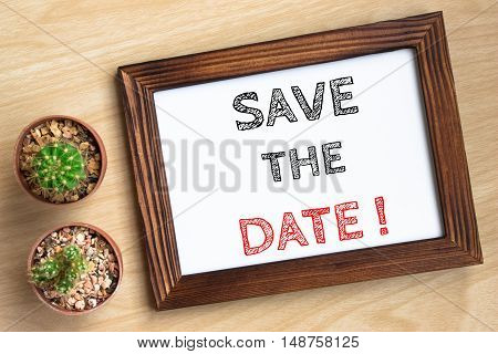 save the date, text message on wood frame board on wood table / business concept / Top view