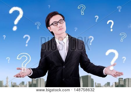 Picture of a pensive young businessman wearing formal suit with question mark on the sky