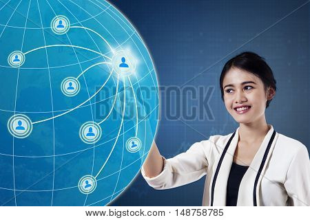 Concept of social media connection. Pretty Asian businesswoman presses social media button on the touch screen
