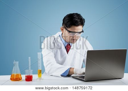 Portrait of male scientist doing research with chemical liquid and laptop computer on the table