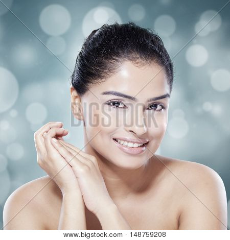 Closeup of gorgeous female model with natural skin smiling at the camera on light glitter background