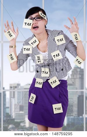 Portrait of stressful businesswoman standing in the office with tax reminders on her body