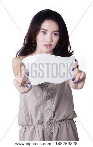 Portrait of a pretty teenage girl showing empty paper in the studio isolated on white background