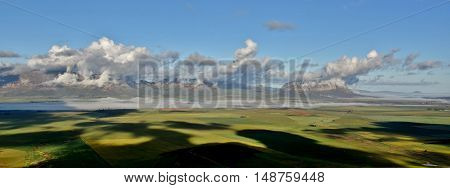 Landscape with green meadows Mountains and clouds