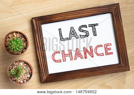last chance, text message on wood frame board on wood table / business concept / Top view