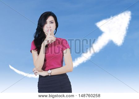 Photo of a female worker showing silence sign with upward arrow on the sky shot outdoors