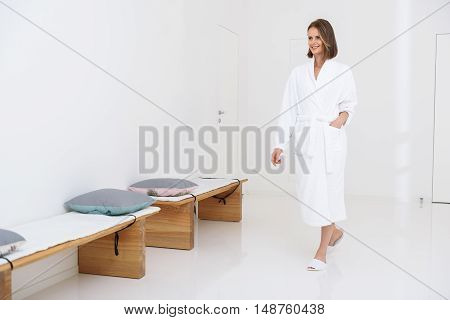 Having spa day of pampering. Beautiful young woman spending time in spa salon and walking along hall to next treatments