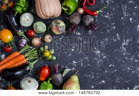 Autumn vegetable harvest. Pumpkin eggplant peppers carrots tomatoes onions garlic beets on a dark background top view. Free space for text