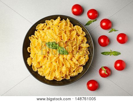 Plate with gnocchi pasta and tomatoes on table