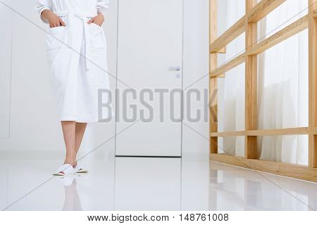 Let is start spa treatments. Cropped photo of woman wearing white bathrobe and spending time at spa, walking down hallway