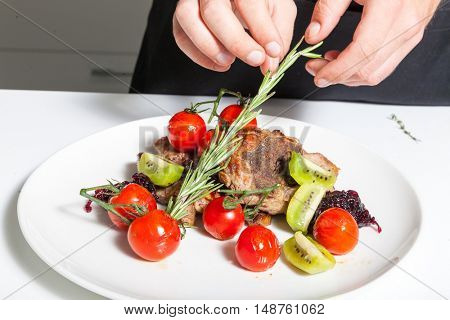 Chef decorating meat dish