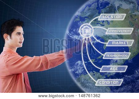 Concept of property value. Young male worker touching property value button and globe on the virtual screen