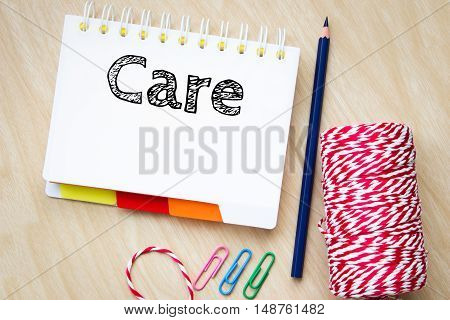Care, text message on white paper and pencil on wood table / business concept