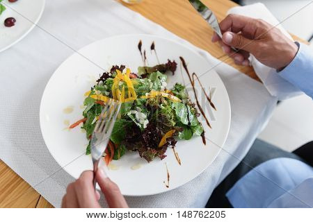 Fresh mixed green salad. Top view of businessman in blue shirt having vegetables salad during lunch at restaurant