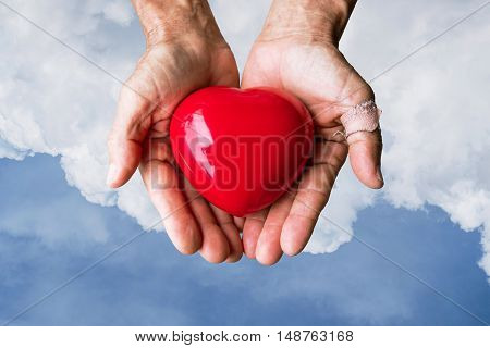 Elderly hands with wound holding red heart heart on blue sky and white clouds