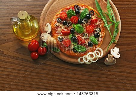 Tasty pizza with vegetables, herbs and oil on wooden background