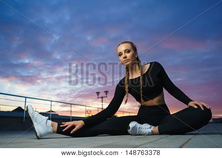Concept: healthy lifestyle sport. Attractive happy girl fitness trainer stretch outdoor workout at modern downtown urban area during sunset.