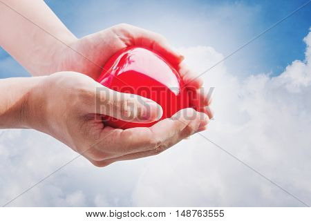 Hand holding red hart on blue sky and white clouds, with bright light