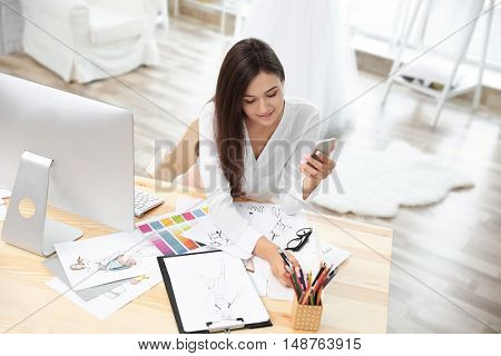 Pretty young dress designer with mobile phone sitting at workplace