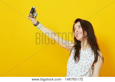 Girl with vintage camera taking photo yellow background.  Teenage girl taking a selfie with retro camera on bright background