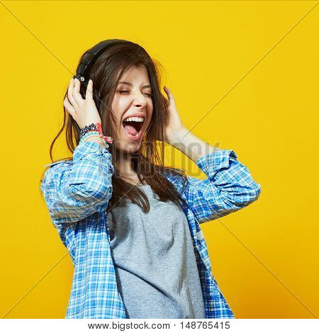 young teenage woman wearing headphones listen to music and sing with open mouth over colorful yellow background