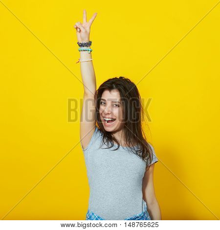 Happy smiling beautiful young woman showing two fingers or victory gesture, isolated over yellow background
