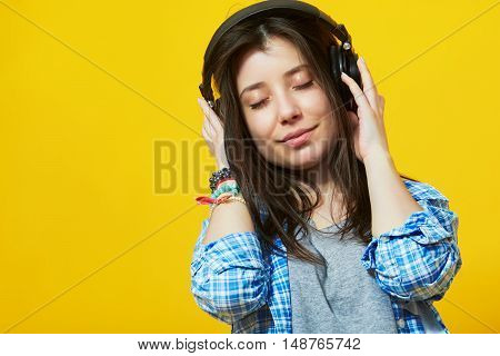 Young beautiful woman in bright outfit enjoying the music over yellow wall with copy space. Studio portrait of a girl with eyes closed wearing headphones