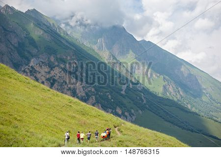 people carrying equipment walking along a footpath in the mountains