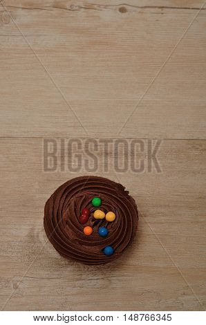Chocolate Cupcake with chocolate frosting and decorated with colorful candy