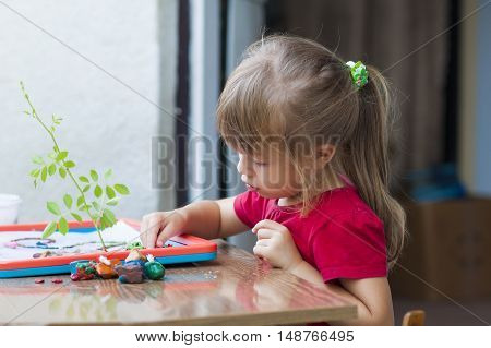 Little cute girl playing table play outside