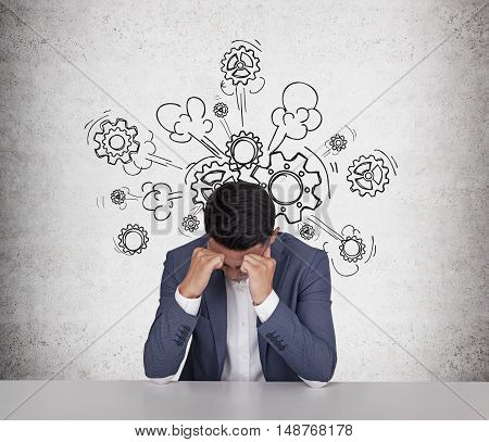 Portrait of stressed out Asian businessman sitting near concrete wall with steam and cog sketches coming out of his head. Concept of overworking