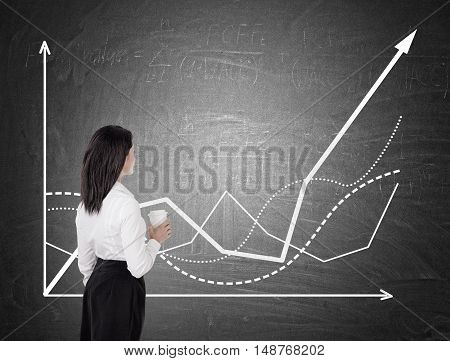 Side view of businesswoman with coffee studying growing graph. Concept of successful company development