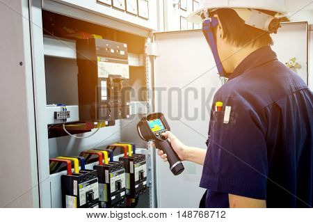 technician use thermal imaging camera to check temperature in factory